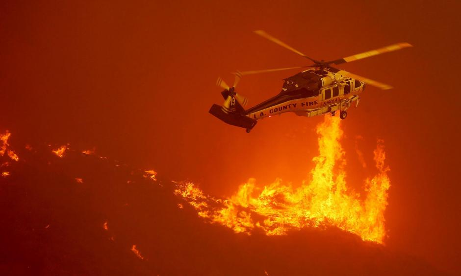 A firefighting helicopter hovers close to the flames from the Sand fire as it burns out of control along Soledad Canyon Road. Photo: Luis Sinco / Los Angeles Times