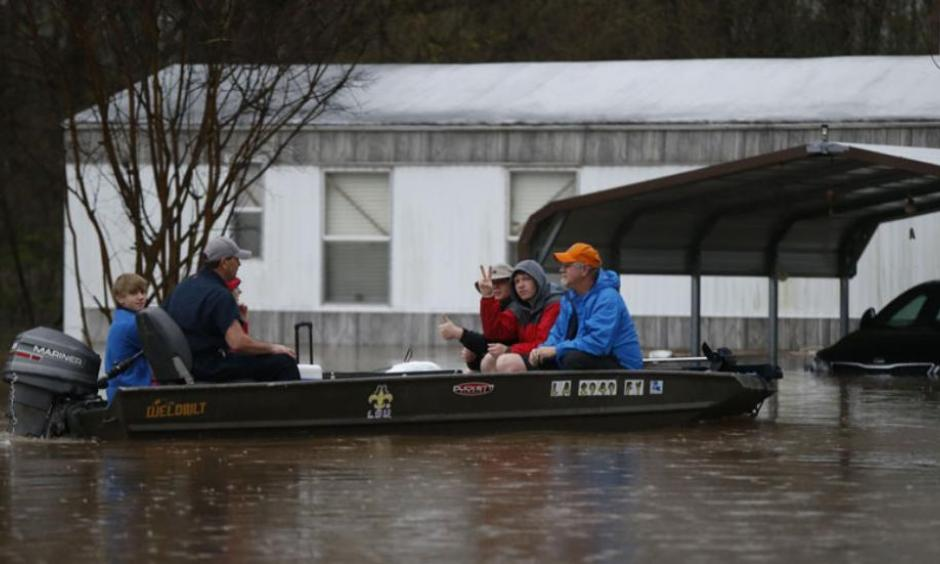 Sarah Yatcko, left, holds her son Tucker Neal as they are evacuated by boat with her father Jim Yatcko, by Bossier County Sheriff personnel during rising floodwaters in Bossier Parish, La., Thursday, March 10, 2016. Photo: AP, Gerald Herbert