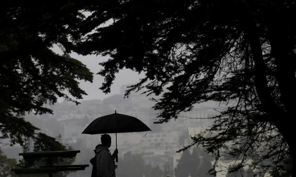 A man and a woman walk together in Alamo Square Park in San Francisco on Thursday evening. Photo: Jeff Chiu, AP