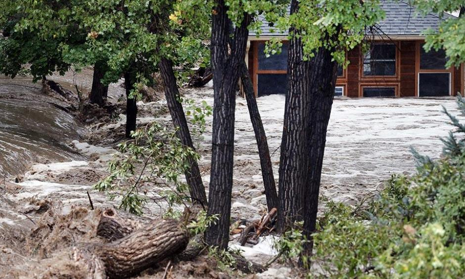 A torrent of water rushes alongside a swamped house following flash flooding near Left Hand Canyon, south of Lyons, Colo., Sept 12, 2013. Photo: Brennan Linsley, AP