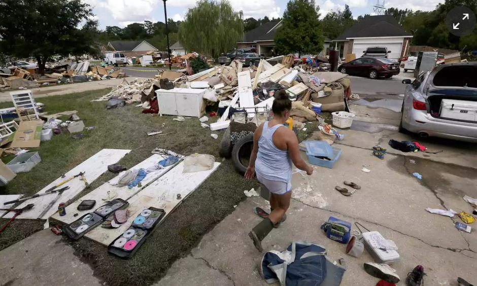 """A resident walks through a flood-damaged neighborhood in Louisiana. The state's governor has requested an addition $2bn in emergency aid from the federal government. """"Simply put, we cannot recover without it,"""" Edwards said at a House subcommittee hearing. Photo: Jonathan Bachman/Reuters"""