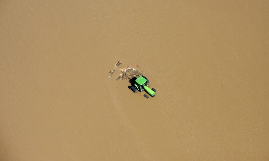 A tractor sits partially submerged in a field after flooding along the South Platte River in Weld County, Colorado near Greeley, on September 14, 2013. Photo: John Wark, AP