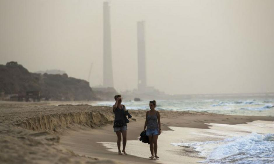 Tourists walk at the shore of the Mediterranean sea in Ashkelon in southern Israel during heavy hazy weather in the region. (photo credit:REUTERS)