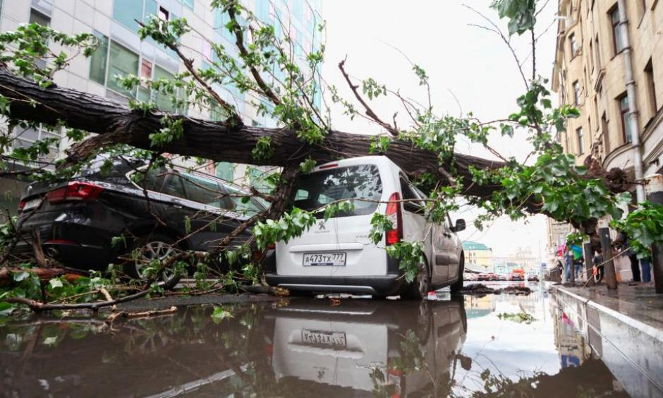 Vehicles are covered with a fallen tree following a storm, in a residential area of Moscow, Russia. Thunderstorms and strong winds buffeted Moscow and its surrounding areas on Monday. Photo: Sergey Vedyashkin, Moscow News Agency photo via AP