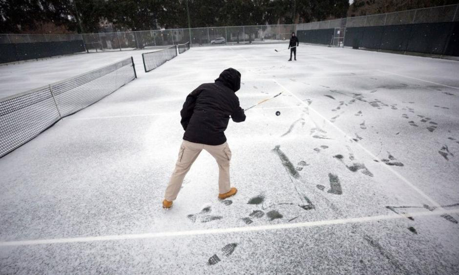 Vincent Sottile, center, and his brother Mike Sottile play hockey on the public tennis courts at Forsyth Park on Wednesday in Savannah, Ga. Photo: Stephen B. Morton, AP