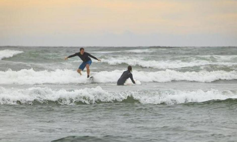 Taking advantage of Nahant Beach's waves on Labor Day morning were Nels Nelson of Somerville and Odette Bakker, visiting from the Netherlands. Photo: Dina Rudick, Globe Staff