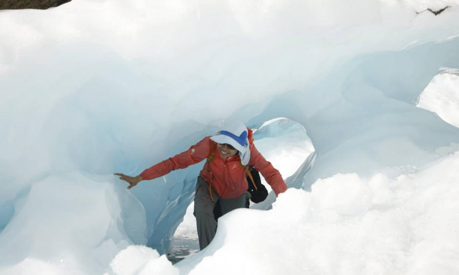 In this Feb. 6, 2016 photo, tourists who have taken a helicopter trip onto the Fox Glacier climb through a hole in the ice in New Zealand. The Fox and Franz Josef glaciers have been melting at such a rapid rate that it has become too dangerous for tourists to hike onto them from the valley floor, ending a tradition that dates back a century. Photo: Nick Perry, AP