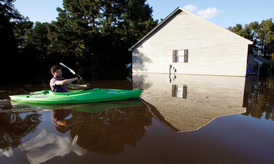 A resident paddles his kayak into his neighborhood to check the condition of his house as river levels rise into town in the aftermath of Hurricane Matthew, in Greenville, North Carolina, Oct. 14, 2016. Photo: Jonathan Drake, Reuters
