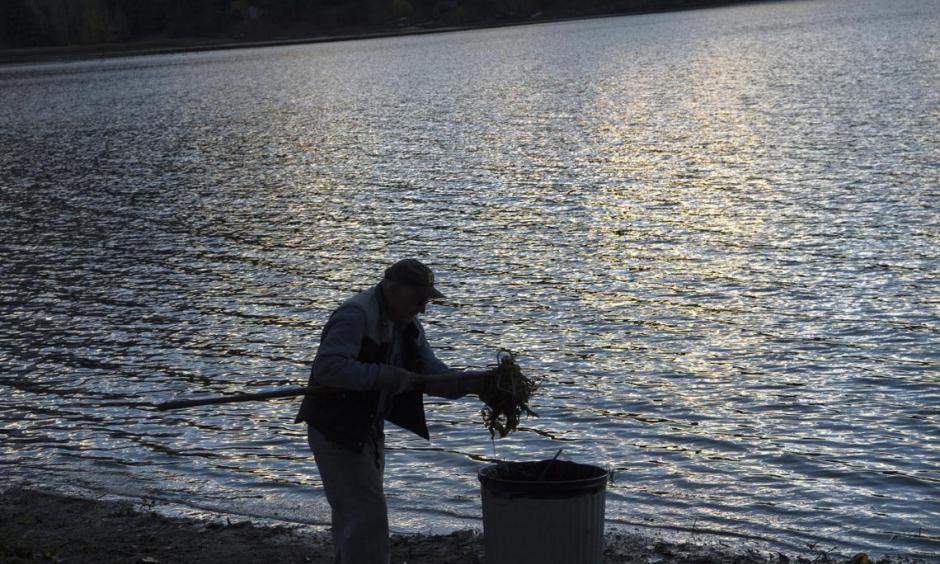 Ralph Sherrill works to clean up debris on the exposed shoreline near the Liberty Lake, Wash., home he shares with his wife, Sandra, on Wednesday, Nov. 11, 2015. The lake recently reported its second lowest level since 1951. (Tyler Tjomsland)