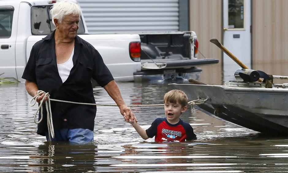 Richard Rossi and his four-year-old great-grandson, Justice, wade through water in search of higher ground after their home flooded in St. Amant, Louisiana. Photo: Jonathan Bachman / Reuters