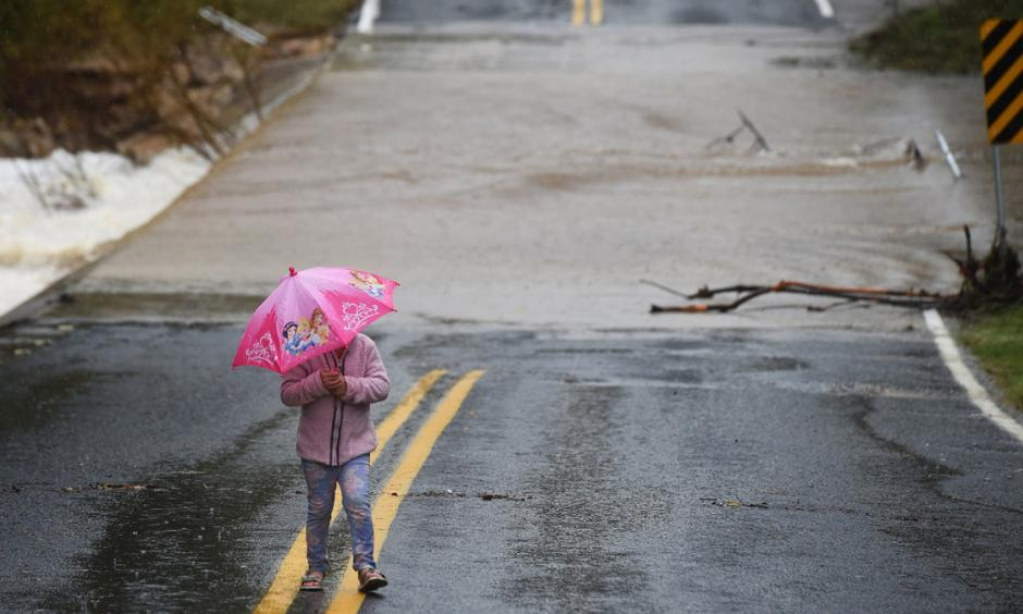 A girl walks near a flooded street in Austin, Texas, on October 24, 2015. Photographer: Jewel Samad/AFP via Getty Images