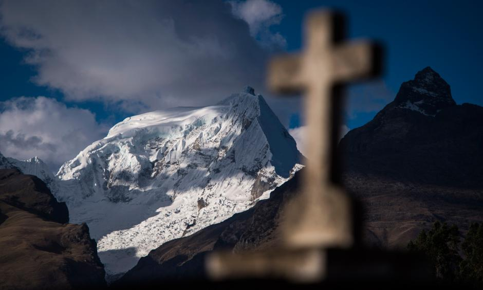 An Andes mountain range and a cross headstone are seen from Cementerio Municipal De Huaraz in Huaraz, in the Ancash region of Peru, on July 13. Photo: Jabin Botsford