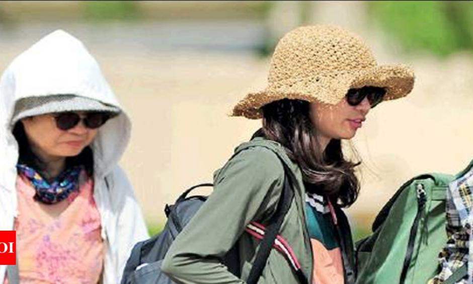 Tourists protect themselves from the heat. Photo: Times of India