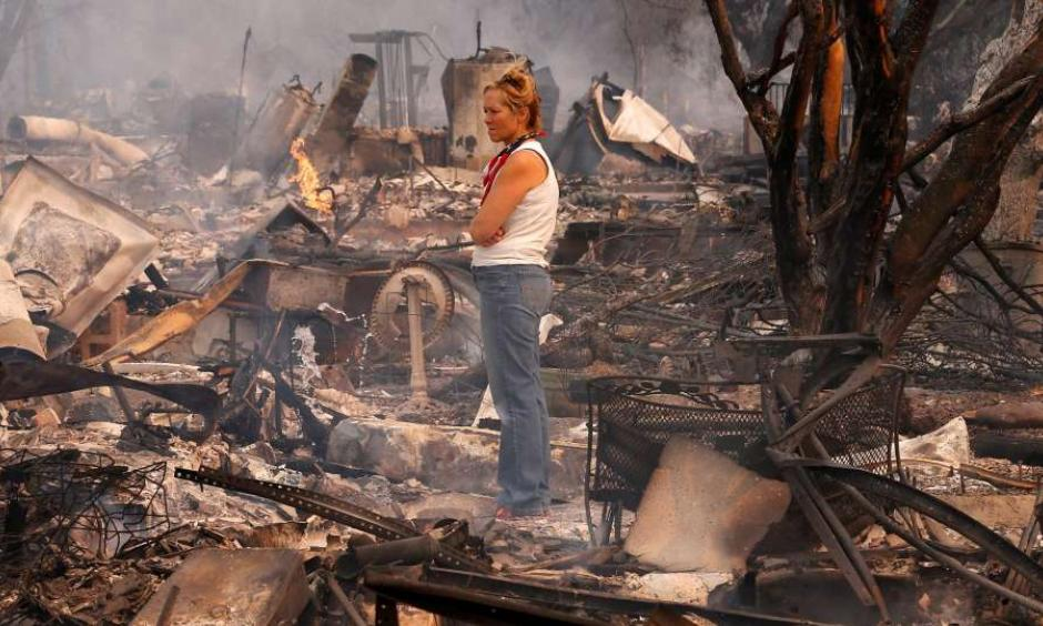 Terrie Burns stands in the middle of her destroyed at the scene of the Tubbs Fire in Santa Rosa, Ca., on Monday October 9, 2017. Massive wildfires ripped through Napa and Sonoma counties early Monday, destroying hundreds of homes and businesses on Monday October 9, 2017. Photo: Michael Macor, The Chronicle