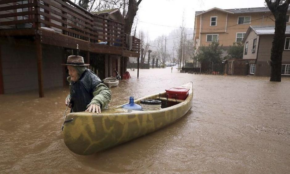 Sycamore Court resident Jesse Hagan evacuates to higher ground from an apartment complex in lower Guerneville, Calif., on Tuesday. Photo: Kent Porter, The Press Democrat
