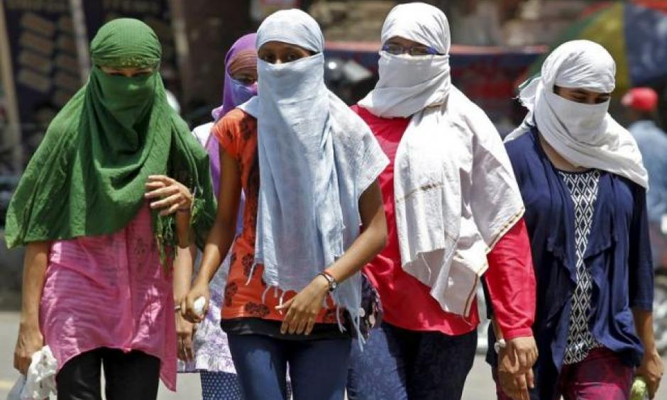 Girls, with faces covered to protect themselves from sun stroke, walk along a road on a hot summer day in Allahabad, India, May 29, 2015. Image:Jitendra Prakash, Reuters