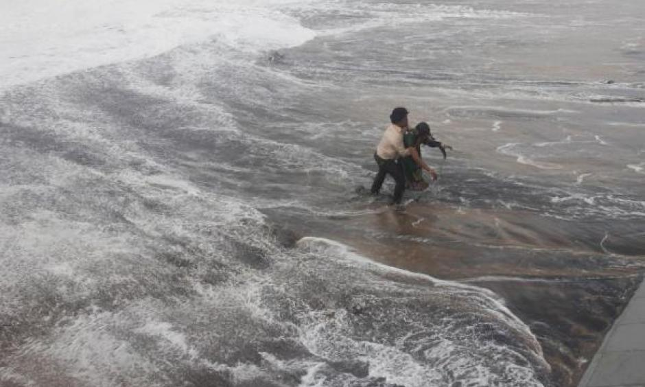 A man carries his wife to a safer ground after a wave hits a beach in Gopalpur in Ganjam district in the eastern Indian state of Odisha October 12, 2014. Image: Stringer, Reuters