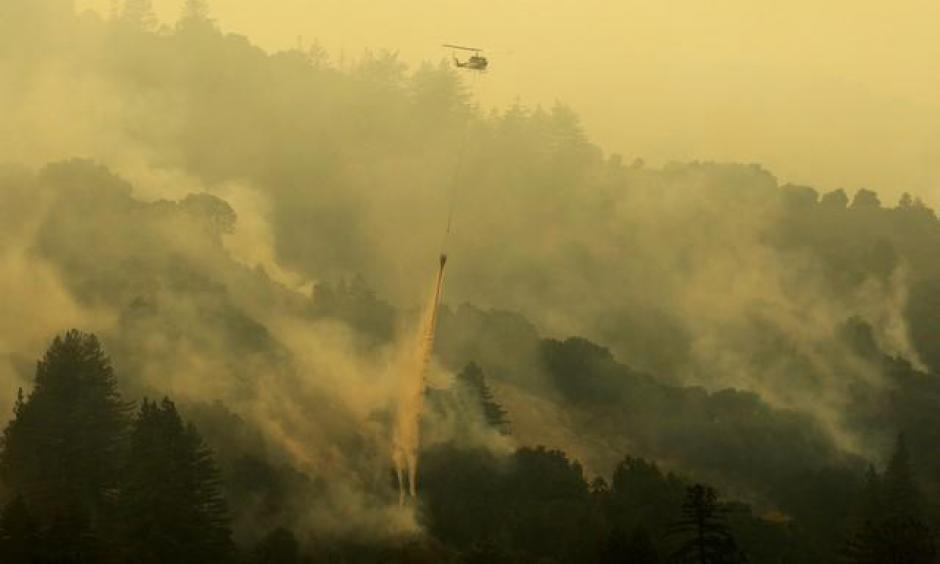 A firefighter stands on steep terrain while fire crews create fire breaks at Garrapata State Park during the Soberanes Fire north of Big Sur, California, U.S. July 31, 2016. Photo: Michael Fiala, Reuters