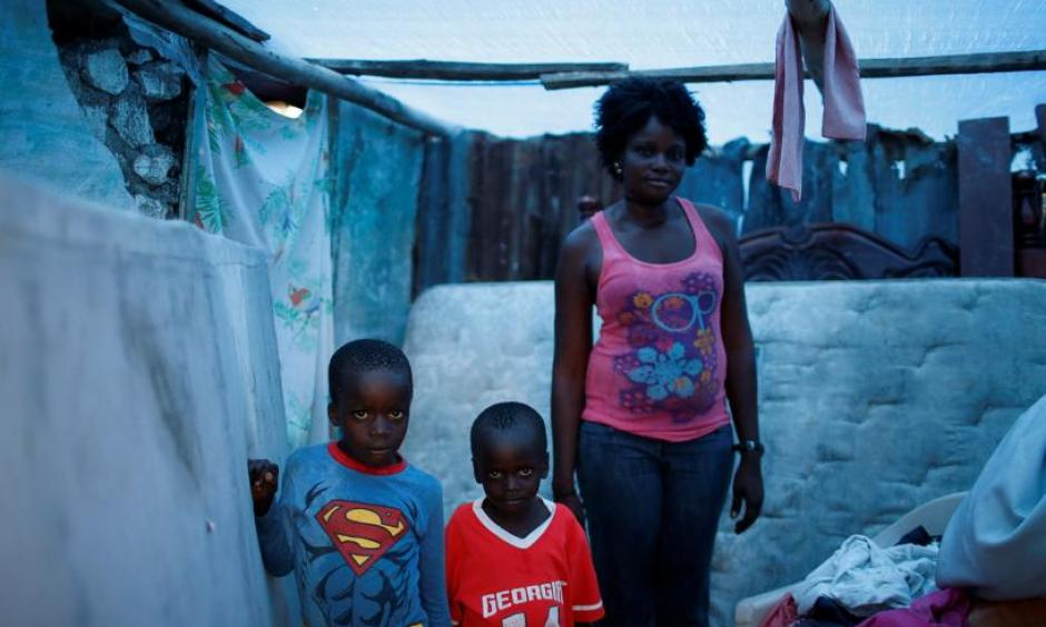 Marie Ange St Juste (R), 29, poses for a photograph with her sons, Kensley, 7 (L), and Peterley, 5, in their destroyed house after Hurricane Matthew hit Jeremie, Haiti, October 17, 2016. 'My house was totally destroyed during the storm,' said St Juste. 'I lost everything, but I was lucky that none of my children died. Now my situation is very bad, we need help.' Photo: Carlos Garcia