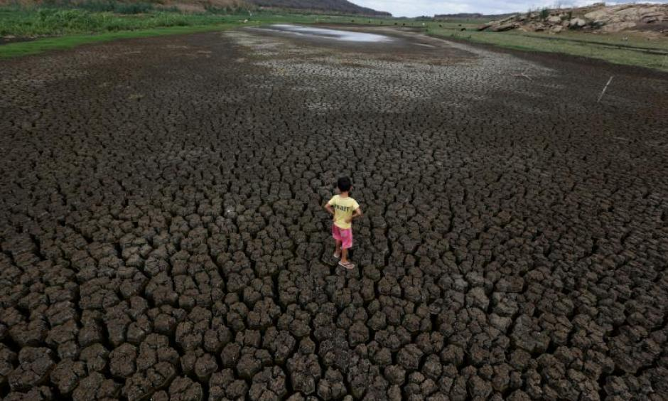 Natan Cabral, 5, stands on the cracked ground of the Boqueirao reservoir in the Metropolitan Region of Campina Grande, Paraiba state, Brazil, February 13, 2017. Photo: Ueslei Marcelino, Reuters