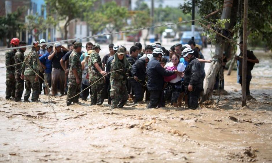 Police help residents cross a flooded street after a massive landslide and flood in the Huachipa district of Lima, Peru, March 17, 2017. Photo: Sebastian Castaneda, Reuters