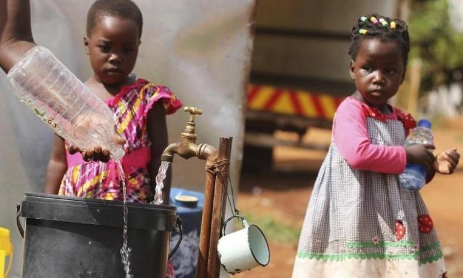 Zimbabwean children watch as their mother collects water from a communal tap in Harare, February 5, 2016. Photo: Reuters, Philimon Bulawayo