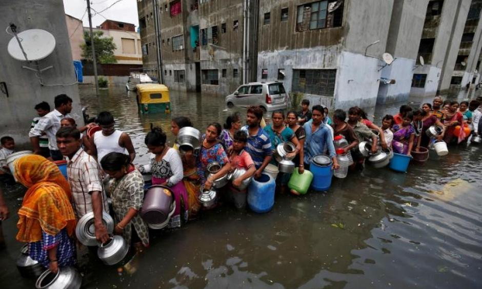 People queue to collect drinking water from a municipal tanker at a flooded residential colony in Ahmedabad, India, July 29, 2017. Photo: Thomson Reuters Foundation