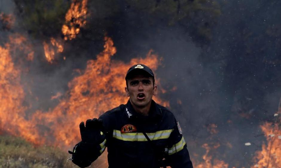 A firefighter reacts as flames rise during a wildfire near the village of Kapandriti, north of Athens, Greece, August 15, 2017. Photo: Alkis Konstantinidis