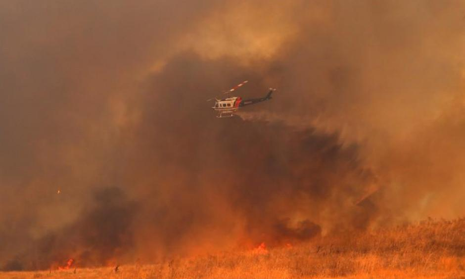 A helicopter drops water on a wind driven wildfire in Orange, California, U.S., October 9, 2017. Photo: Mike Blake, Reuters