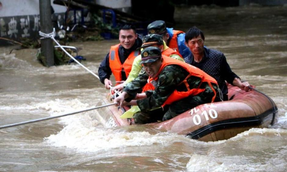 Rescuers grab a rope to prevent a raft carrying residents from being flushed away as residents are evacuated from a flooded area in Jiujiang, Jiangxi Province, China, June 19, 2016. Photo: Reuters / Stringer