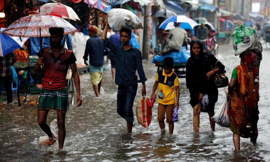 People walk on the water as roads are flooded due to heavy rain in Dhaka, Bangladesh July 26, 2017. Photo: Mohammad Ponir Hossain, Reuters
