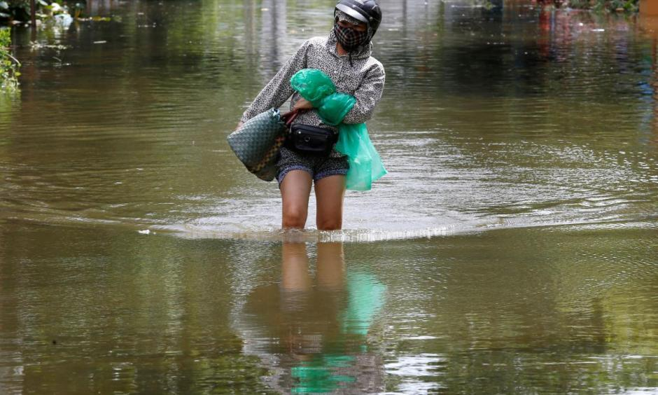 A woman wades through a flooded village after heavy rainfall caused by tropical storm Son Tinh in Ninh Binh province, Vietnam, July 22, 2018. Photo: Reuters/Kham