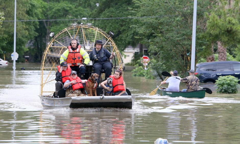 People and their pets are rescued from their homes near Nanes at Baltic in Houston, Texas, Wednesday, April 20, 2016.Thousands of people have been evacuated from their homes and major highways were closed after the rains that started Sunday overwhelmed Houston's bayous. Forecasters have issued another flash flood watch for Houston through Wednesday night. Photo: Steve Gonzales/Houston Chronicle via AP