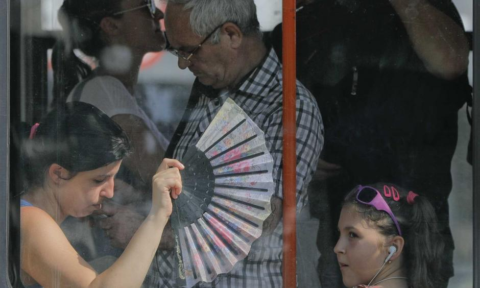"A woman uses a fan to cool herself and a child wile ridding on a tram in Bucharest, Romania, Friday, Aug. 4, 2017. Romanian meteorologists issued an extreme temperatures warning, with 42 Celsius (107.6 F) forecast for parts of western Romania and placing 12 counties under a ""red code"" heat alert for the next two days. Photo: Vadim Ghirda, AP"