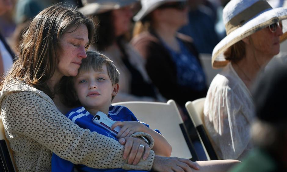 Laura Schulze, above, holds her son Zachary, 8, during the Day of Remembrance at Santa Rosa Junior Col lege, where hundreds of community members, officials and first responders gathered in Bailey Field, below. Photo: Leah Millis, The Chronicle