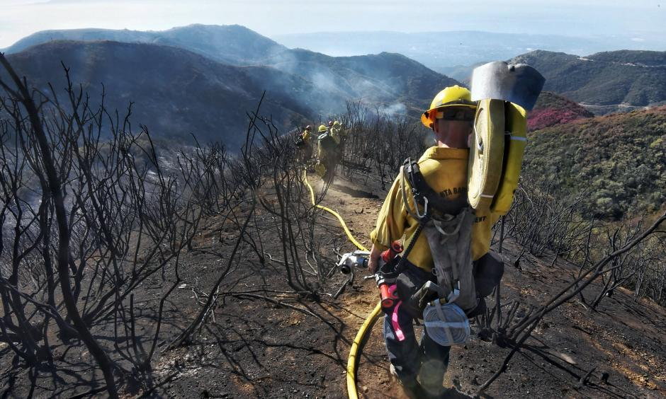 Santa Barbara County Firefighters haul dozens of pounds of hose and equipment down steep terrain to root out and extinguish smoldering hot spots in Santa Barbara on Tuesday, Dec. 19, 2017. Officials estimate that the Thomas Fire will grow to become the biggest in California history before full containment. Photo: Mike Eliason, AP