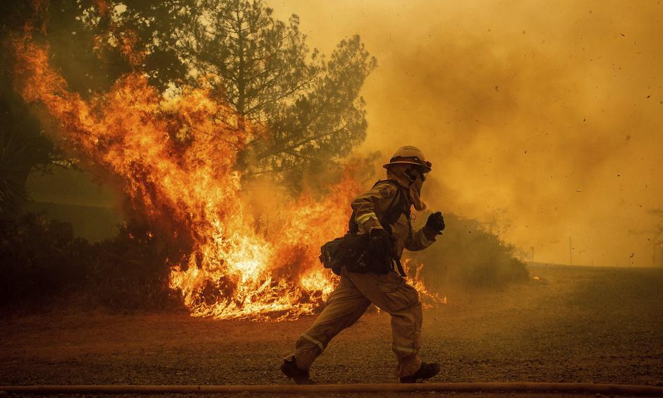 A firefighter runs while trying to save a home as a wildfire tears through Lakeport (Lake County) on Tuesday. The shift in the jet stream that's driving the West's stagnant hot weather is almost certainly the result of global warming, climate scientists say. Credit: Noah Berger, Associated Press