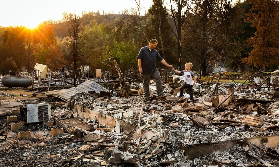 Five-year-old Daniel Wood shows his grandfather, Matthew Schjoth, a wrench he found as they look through the remains of their home on Harlan Drive in Redding that was destroyed in the Carr Fire. Credit: San Francisco Chronicle
