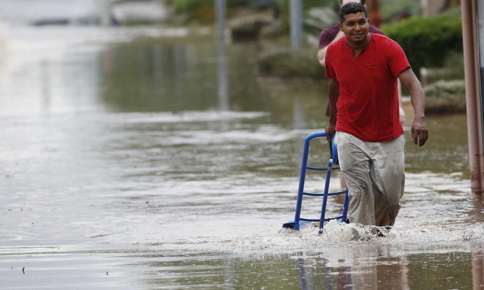 A pedestrian walks through a flooded street with a hand truck to get sand bags to deliver to local businesses during a flash flood as a result of heavy rains from tropical storm Rosa Tuesday, Oct. 2, 2018, in Phoenix. Photo: Ross D. Franklin, AP