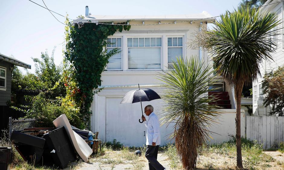 Berhane Woldeabzghi takes cover from the sun as he strolls through his Oakland neighborhood. Photo: Lea Suzuki, The Chronicle