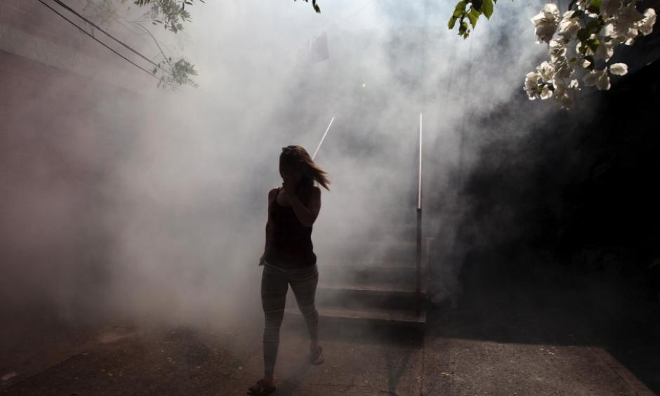 A woman walks away from her apartment as health workers fumigate as part of preventive measures against the Zika virus in Soyapango, El Salvador. Photo: Jose Cabezas, Reuters