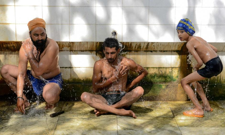 Two Indian men and a boy cool off in Amritsar, India, on Tuesday. Photo: Narinder Nanu, AFP/Getty Images