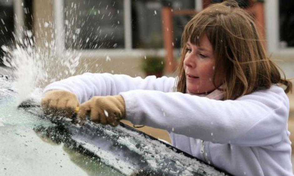 Krystal Wright scrapes ice from her car's windshield Friday, Nov. 27, 2015 in Wichita, Kan. The winter weather left a layer of ice on roads and cars early Friday morning after a heavy rain on Thanksgiving day that set a record with over 2 inches of rain. Photo: Brian Corn, The Wichita Eagle via AP