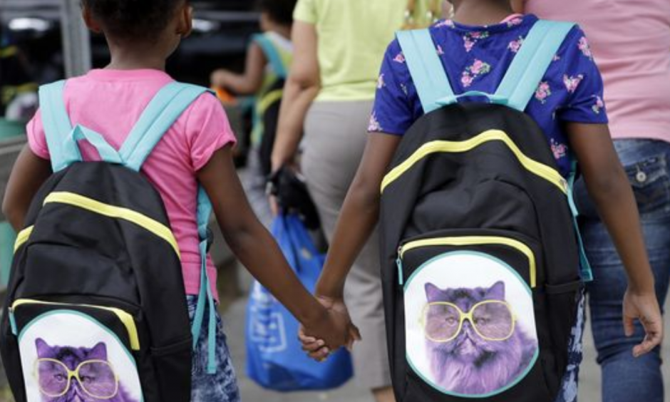 In this file photo, children in Miami hold hands as they walk with their new book bags. Photo: Lynne Sladky, AP