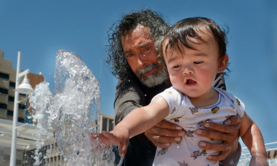 Ernest Espinosa and his grandson, Mariano Espinosa, 1, beat the heat by playing in the Civic Plaza fountain Monday. Albuquerque hit a record high of 98 degrees Monday, but temperatures will drop slightly this week as a cold front pushes into New Mexico. Credit: Greg Sorber, Albuquerque Journal