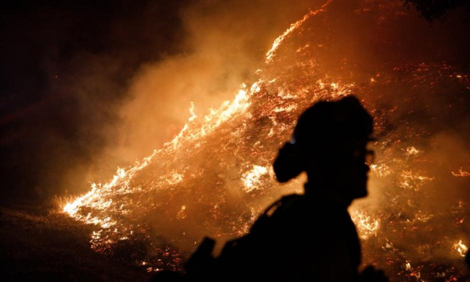 Firefighters stand watch by a fire line along Mayacama Club Drive as the Kincade Fire burns in the outskirts of Santa Rosa, Calif., on Oct. 28, 2019. Credit: Dai Sugano/Bay Area News Group