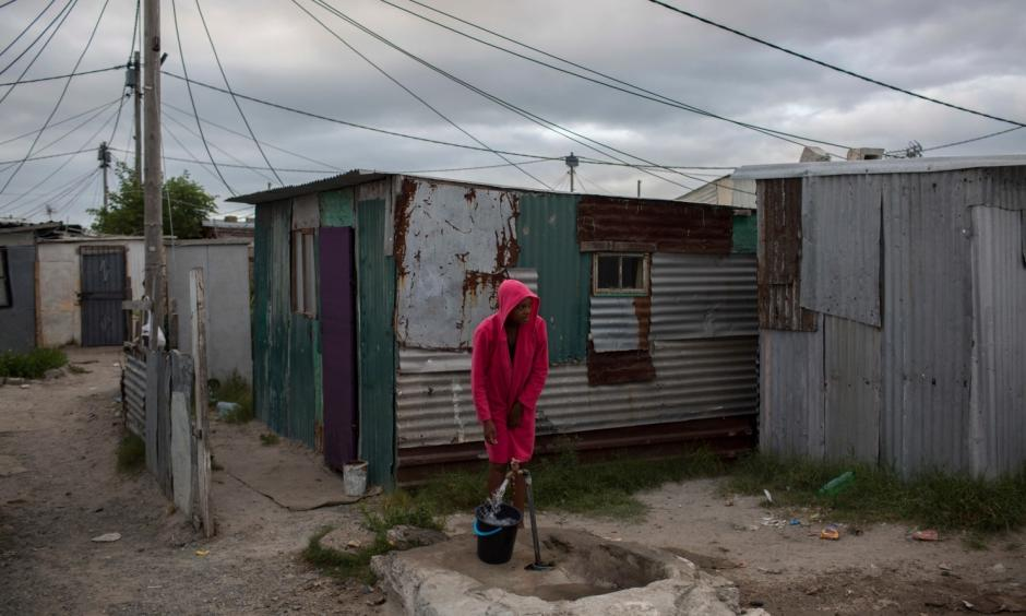 In this Feb. 2, 2018 photo, a woman collects water in a settlement near South Africa's drought-hit city of Cape Town. About a quarter of Cape Town's population lives in the informal settlements, where they get water from communal taps instead of individual taps at home like in the richer suburbs. And they use 4.5 percent of the total water consumption. Photo: Bram Janssen, AP