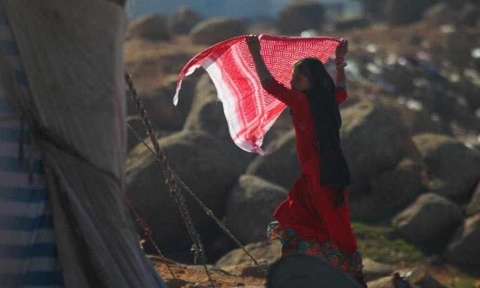 An internally displaced girl carries a scarf as she stands outside tents at a makeshift refugee camp in Sinjar town, in Idlib province, Syria, November 20, 2015. Photo: Ammar Abdullah, Reuters