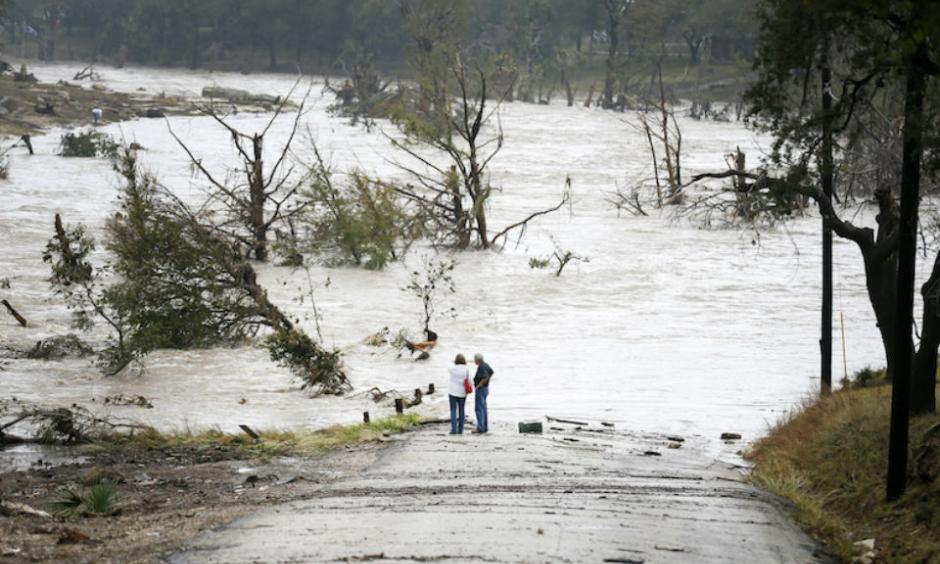 Jim Richardson and his wife Jeannette look on as the Blanco River recedes after the flash flood in Wimberly, Texas Friday, Oct. 30, 2015. A fast-moving storm packing heavy rain and destructive winds overwhelmed rivers and prompted evacuations Friday in the same area of Central Texas that saw devastating spring floods. Image credit: Ricardo Brazziell/Austin American-Statesman via AP.