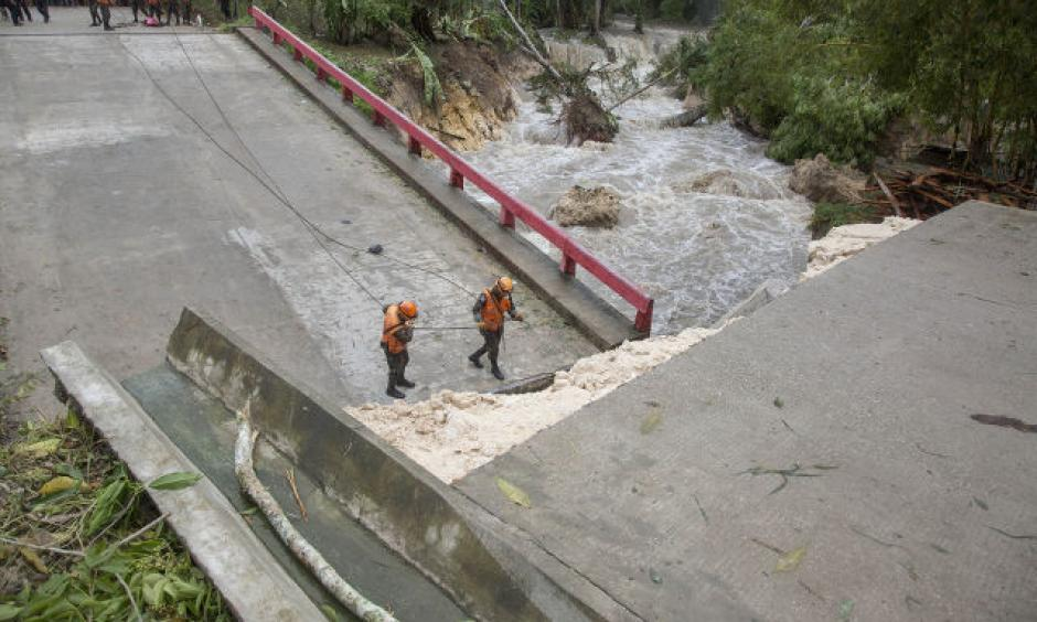 A handout picture made available by the National Coordination for Disaster Reduction of Guatemala (CONRED) shows members of the national army emergency and rescue team (UHR) working at a fallen bridge damaged after strong rains hit the region, following the passage of Tropical Storm Earl, in Melchor de Mencos, Guatemala, August 4, 2016. Photo: CONRED / EPA